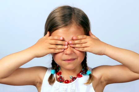 Little girl with her hands covering her eyes photo