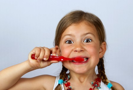 Liitle girl brushing her teeth vigorously with a red toothbrush Stock Photo - 6990545