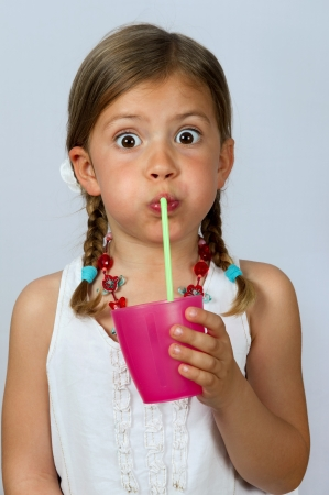 Little girl drinking from a cup with a straw photo