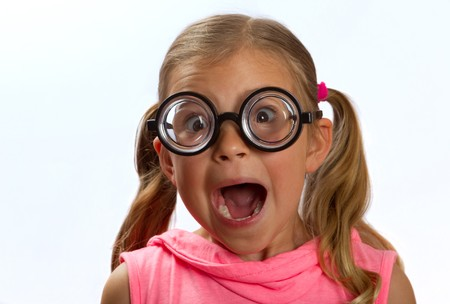 aghast: Little girl wearing big round glasses and making a silly expression