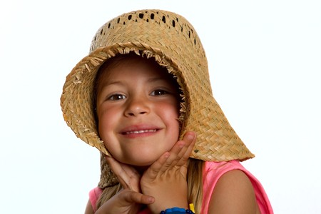 Portrait of a pretty little girl wearing a straw hat and pulling it over her ears photo