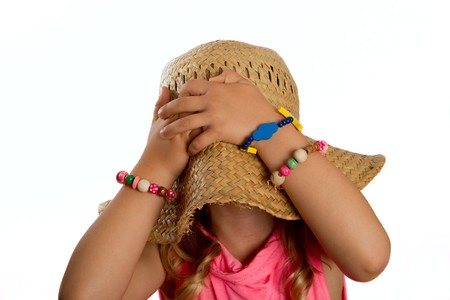 Portrait of a little girl pulling a straw hat over her head and hiding her face photo