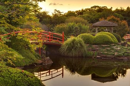 ponte giapponese: Tranquil giardino Japaneese il tramonto con riflessi nell'acqua