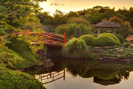 garden pond: Tranquil Japaneese garden on dusk with reflections in the water Stock Photo
