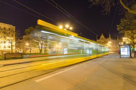 tramway: Night motion blur light trails at Poznan tram stop