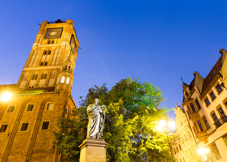 Colorful night view of Nicolaus Copernicus Monument and Old Market town hall in Torun, Poland Stock Photo