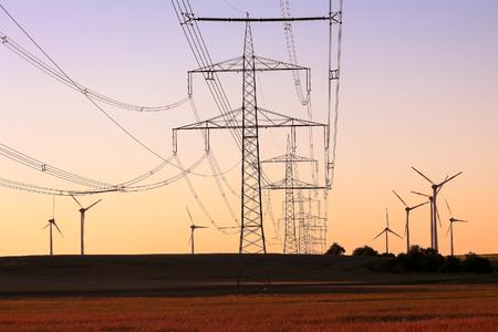 Koncepcja energii zielonej - linie energetyczne wysokiego napięcia z tłem farm wiatrowych