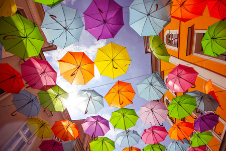 Colorful open umbrellas hanging in the air