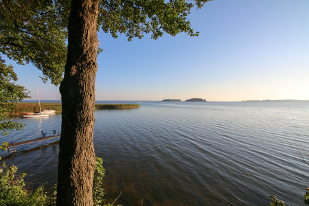 masuria: A scenic early morning panorama of a Masurian lake with two islands visible in the background.