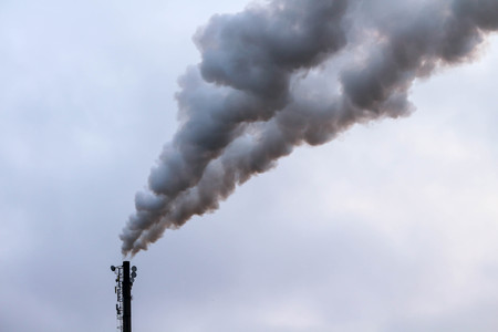 Thick clouds of smoke billowing out of an industrial chimney