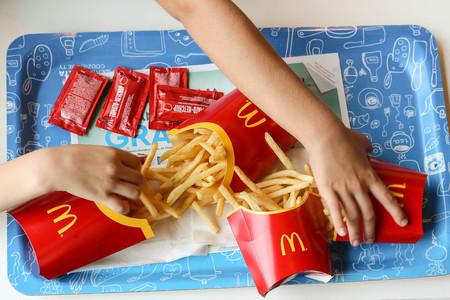 Children's hands reaching for chips in McDonald's restaurant Editorial