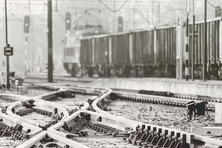 Railway tracks crossing with a blurred cargo train in the background