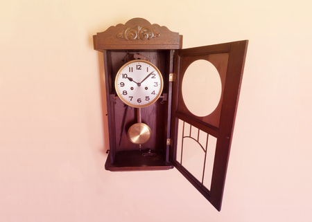 Antique, wooden wall clock with the front glass opened on a warm, pastel background