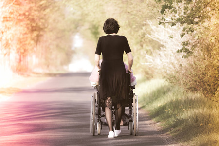 A woman pushing a wheelchair with a disabled person