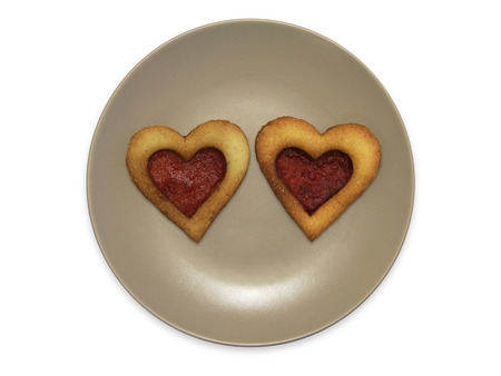 teacake: the smiley in the form of plates with cookies, isolated on white background, heart shaped shortbread cookie with jam filling