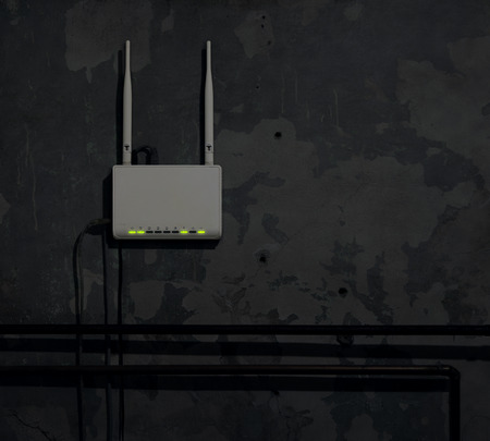 gigabit: Wi-Fi router on an old wall in a dark room - background Stock Photo