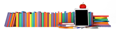 colorful books in a row with the tablet in the foreground, school supplies and an apple - back to school, isolated on white background 版權商用圖片