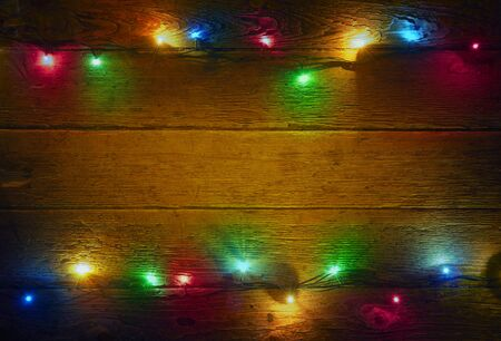 Christmas lights over dark background. Colorful lights on rustic wooden background for xmas and new year design. Merry Christmas vintage card. Old wooden table. Natural pattern. Wood texture Stockfoto