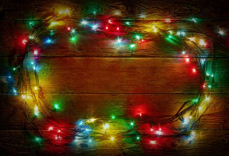 Colorful lights on rustic wooden background for christmas and new year design. Merry Christmas vintage card. Xmas lights over dark background. Old wooden table. Wood texture. Natural pattern Stockfoto