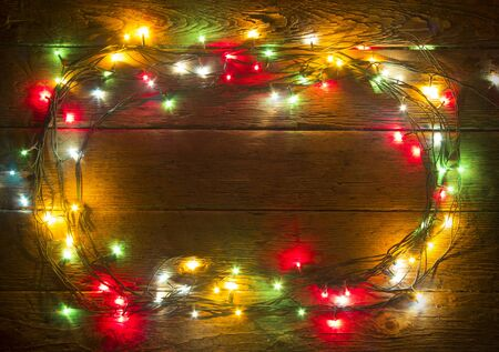 Christmas lights on plank background. Holiday backdrop. Colorful lights on rustic wooden background for xmas, new year design. Merry Christmas vintage card. Old wooden table. Wood texture