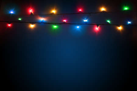 Multicolored christmas lights on a dark blue background. Colorful background for new year design. Merry christmas greeting card. Garlands glowing with lights. Banner, poster Stockfoto
