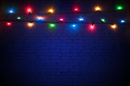 Multicolored Christmas lights on a blue brick wall background. Colorful background for New Year's design. Merry Christmas greeting card. Garlands are glowing with lights. Banner, poster Stockfoto - 159178266