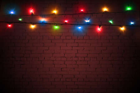 Multicolored Christmas lights on a brown brick wall background. Colorful background for New Year's design. Garlands are glowing with lights. Merry Christmas greeting card. Banner, poster Stockfoto