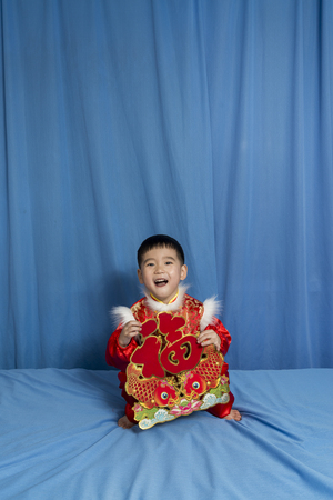 national fruit of china: Child holding the Chinese new year blessing decoration