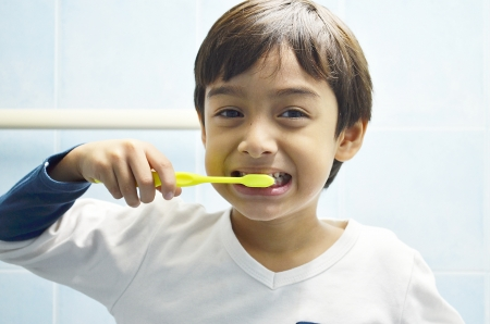 Kid brushing his teeth with smiling photo
