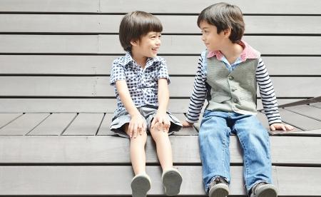 Aziatische sibling zitten samen met glimlach Stockfoto