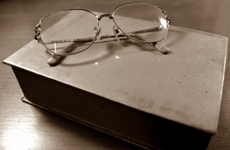 Glasses on the old book sepia photo
