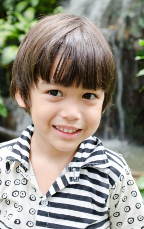 Little asian boy smiling portrait with waterfall  Stock Photo