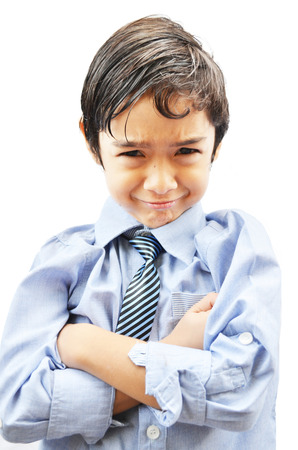 Little boy with a grumpy expression on white background photo