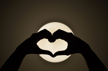 sihouette: Heart shape woman hand making on the light  Silhouette Stock Photo