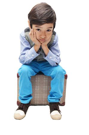 Little boy  sitting on luggage with sad face on white background photo