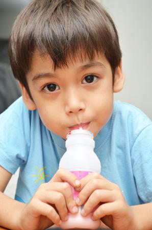 favor: Little boy drinking milk strawberry favor Stock Photo