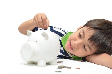 piggy bank: Little boy saving money in piggy bank
