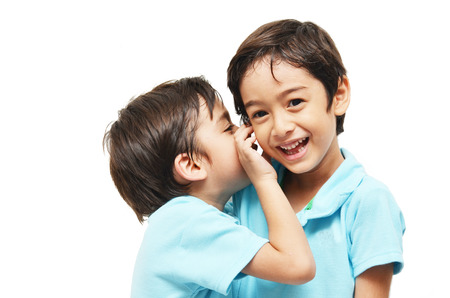 Little sibling boys sharing a secret on white background photo