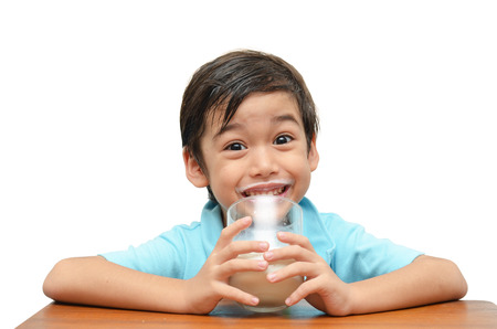 little boy drinks milk on white background