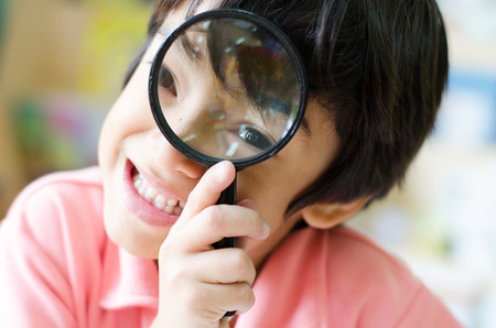 distort: Little boy with magnifier on eyes close up
