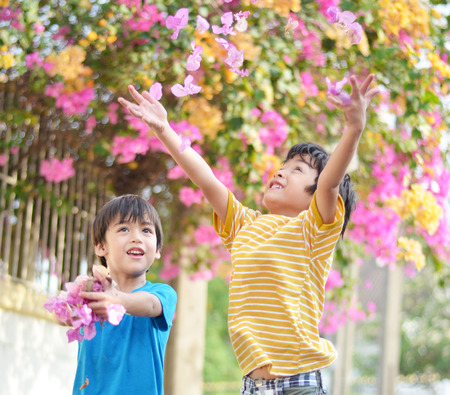 Little sibling boy throw flowers in to the air  photo