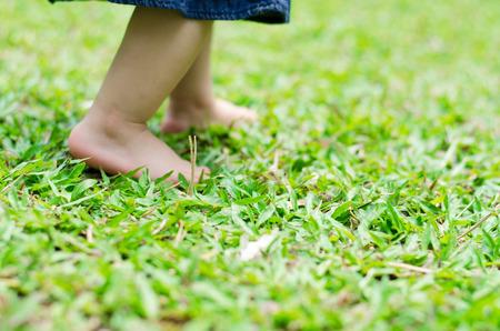 Kleine voeten baby lopen op gras Stockfoto
