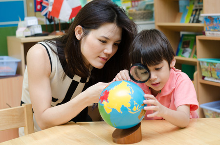Portrait student looking at globe while listening to teacher  photo