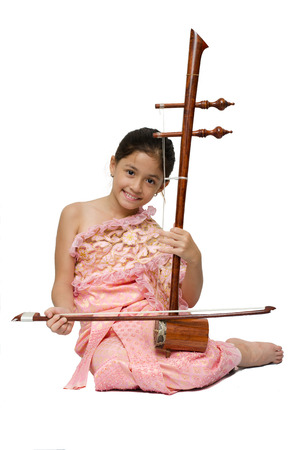 thai musical instrument: Little girl playing fiddle Thai instrument on white background