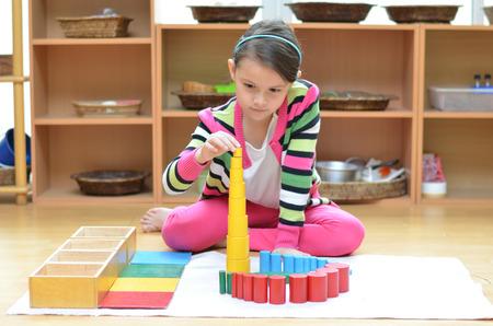 Handje meisje bouwen toren gemaakt van montessori educatief materiaal Stockfoto