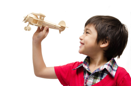 little boy playing with a toy airplane. Isolated on white background photo
