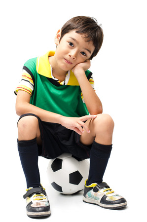 Little boy sitting on football on white background photo