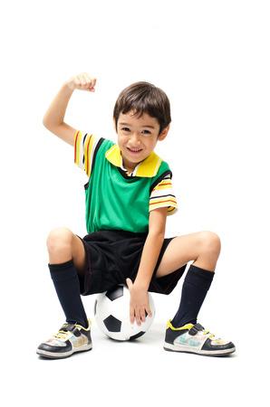 Little boy sitting on football on white background Stock Photo