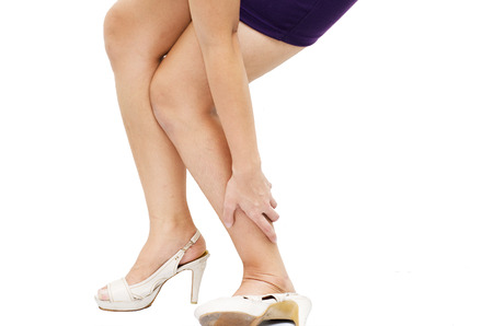 hurting: Woman having ankle pain on white background   Stock Photo