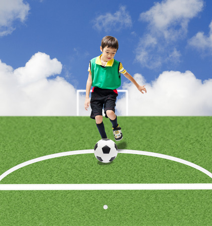 Little boy kicking football to goal photo